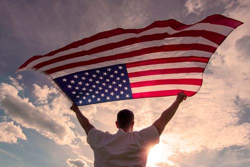 man holding an American flag after gaining visa with help of Nashville immigration lawyer