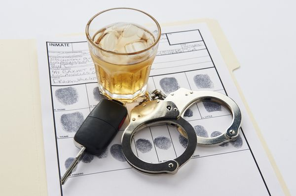 booking papers, handcuffs, alcoholic beverage - concept of court process for dui cases