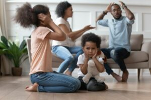 couple arguing with two children in foreground - domestic violence concept