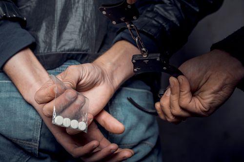 man being arrested for drug possession - Nashville drug possession defense lawyer concept